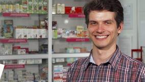 Ευτυχής όμορφη τσάντα αγορών εκμετάλλευσης χαμόγελου ατόμων στο φαρμακείο απόθεμα βίντεο
