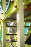 Ευτυχής όμορφος λίγο redhead κορίτσι αναρριχείται στη φωτογραφική διαφάνεια στην παιδική χαρά στοκ εικόνες