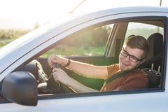 Ευτυχής όμορφος νεαρός άνδρας σε μια καφετιά μπλούζα που οδηγεί ένα αυτοκίνητο Στοκ εικόνα με δικαίωμα ελεύθερης χρήσης