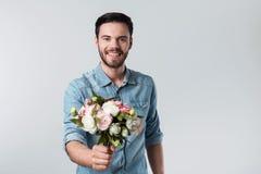 Ευτυχής όμορφος νεαρός άνδρας που κρατά μια δέσμη των λουλουδιών Στοκ Εικόνες