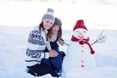 Ευτυχής όμορφος οικογενειακός χτίζοντας χιονάνθρωπος στον κήπο, χειμώνας, mom α Στοκ Φωτογραφίες