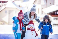 Ευτυχής όμορφος οικογενειακός χτίζοντας χιονάνθρωπος στον κήπο, χειμώνας, Στοκ Φωτογραφία