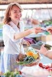 Ευτυχής ώριμη γυναίκα που πληρώνει για τα φρέσκα οργανικά λαχανικά σε μια τοπική αγορά στοκ εικόνα