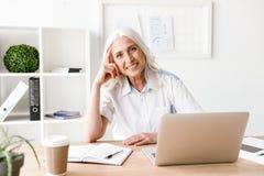 Ευτυχής ώριμη γυναίκα που χρησιμοποιεί το φορητό προσωπικό υπολογιστή Στοκ Εικόνα