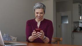 Ευτυχής ώριμη γυναίκα που χρησιμοποιεί το smartphone στο σπίτι φιλμ μικρού μήκους