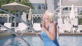 Ευτυχής ώριμη χαλάρωση ζευγών στη λίμνη στο ξενοδοχείο σύνθετο από κοινού Ελκυστική ανώτερη γυναίκα που κάνει ηλιοθεραπεία και πο απόθεμα βίντεο