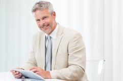 Ευτυχής ώριμος επιχειρηματίας με την ταμπλέτα Στοκ Εικόνες