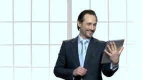 Ευτυχής ώριμος επιχειρηματίας που μιλά μέσω της ταμπλέτας PC απόθεμα βίντεο