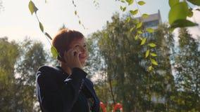 Ευτυχής redhead γυναίκα που καλεί και που μιλά στο τηλέφωνο φιλμ μικρού μήκους