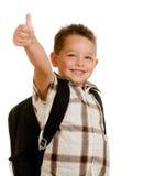 Ευτυχής schoolboy που φορά backpack το δόσιμο φυλλομετρεί επάνω Στοκ φωτογραφία με δικαίωμα ελεύθερης χρήσης