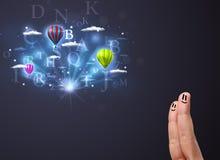 Ευτυχή δάχτυλα smiley που εξετάζουν τα μπαλόνια ζεστού αέρα στο νεφελώδες s Στοκ φωτογραφία με δικαίωμα ελεύθερης χρήσης