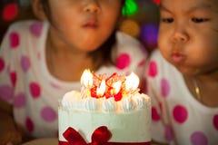Ευτυχή δίδυμα δύο ασιατικά μικρά κορίτσια που γιορτάζουν τα γενέθλια Στοκ Φωτογραφία