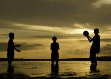 Ευτυχή αγόρια εικόνας σκιαγραφιών που παίζουν το ποδόσφαιρο παραλιών στο χρόνο αυγής με το όμορφο υπόβαθρο ανατολής Στοκ φωτογραφία με δικαίωμα ελεύθερης χρήσης