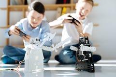 Ευτυχή αγόρια που παίζουν με τα νέα παιχνίδια ρομπότ τους Στοκ Εικόνες