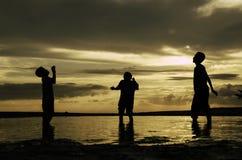 Ευτυχή αγόρια σκιαγραφιών που περιμένουν να πιάσει μια σφαίρα όμορφο υπόβαθρο ηλιοβασιλέματος ανατολής με τα δραματικά σύννεφα Στοκ Φωτογραφία