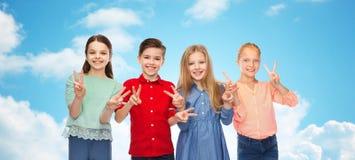 Ευτυχή αγόρι και κορίτσια που παρουσιάζουν σημάδι χεριών ειρήνης Στοκ Εικόνες