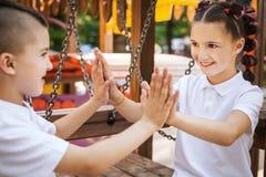 Ευτυχή αγόρι και κορίτσι που παίζουν ένα παιχνίδι με τα χέρια στοκ φωτογραφίες