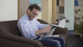 Ευτυχή ανέκδοτα ανάγνωσης ατόμων στην εφημερίδα, το ελεύθερο χρόνο και τη χαλάρωση στο σπίτι απόθεμα βίντεο