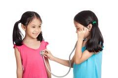 Ευτυχή ασιατικά κορίτσια διδύμων με το στηθοσκόπιο Στοκ φωτογραφία με δικαίωμα ελεύθερης χρήσης