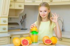 ευτυχή βασικά μικρά πορτοκάλια κοριτσιών καρπού παιδιών Το κορίτσι συμπίεσε το φρέσκο πορτοκάλι Στοκ Εικόνες