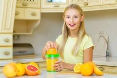 ευτυχή βασικά μικρά πορτοκάλια κοριτσιών καρπού παιδιών Το κορίτσι συμπίεσε το φρέσκο πορτοκάλι Στοκ φωτογραφίες με δικαίωμα ελεύθερης χρήσης