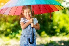 Ευτυχή γέλια και παιχνίδια κοριτσιών παιδιών κάτω από τη θερινή βροχή με ένα umbr Στοκ εικόνα με δικαίωμα ελεύθερης χρήσης