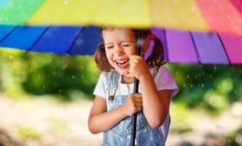 Ευτυχή γέλια και παιχνίδια κοριτσιών παιδιών κάτω από τη θερινή βροχή με ένα umbr Στοκ φωτογραφία με δικαίωμα ελεύθερης χρήσης