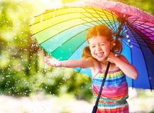 Ευτυχή γέλια και παιχνίδια κοριτσιών παιδιών κάτω από τη θερινή βροχή με ένα umbr Στοκ Φωτογραφία