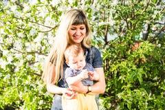 Ευτυχή γυναίκα και παιδί στον όμορφο ανθίζοντας κήπο άνοιξη Έννοια οικογενειακών διακοπών το λουλούδι ημέρας δίνει το γιο μητέρων Στοκ Φωτογραφία