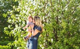 Ευτυχή γυναίκα και παιδί στον όμορφο ανθίζοντας κήπο άνοιξη Έννοια οικογενειακών διακοπών το λουλούδι ημέρας δίνει το γιο μητέρων Στοκ φωτογραφίες με δικαίωμα ελεύθερης χρήσης