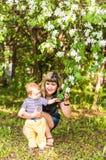 Ευτυχή γυναίκα και παιδί στον όμορφο ανθίζοντας κήπο άνοιξη Έννοια οικογενειακών διακοπών το λουλούδι ημέρας δίνει το γιο μητέρων Στοκ Εικόνα