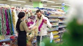 Ευτυχή διακοσμήσεις και δώρα Χριστουγέννων αγοράς ζευγών αγάπης για τα Χριστούγεννα απόθεμα βίντεο