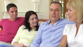 Ευτυχή ζεύγη που χαλαρώνουν στον καναπέ απόθεμα βίντεο