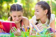 Ευτυχή ισπανικά κορίτσια που σύρουν και που μελετούν στο πάρκο Στοκ Εικόνα