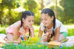 Ευτυχή ισπανικά κορίτσια που σύρουν και που μελετούν στο πάρκο Στοκ Εικόνες
