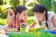 Ευτυχή ισπανικά κορίτσια που σύρουν και που μελετούν στο πάρκο Στοκ φωτογραφία με δικαίωμα ελεύθερης χρήσης