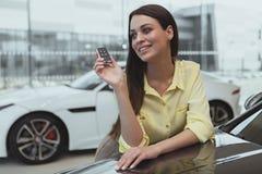 Ευτυχή κλειδιά αυτοκινήτων εκμετάλλευσης γυναικών για το νέο αυτοκίνητό της στοκ φωτογραφίες