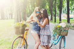 Ευτυχή κομψά κορίτσια boho με κινητό στα ποδήλατα στο πάρκο Στοκ Εικόνες