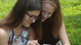 Ευτυχή κορίτσια εφήβων με το κινητό τηλέφωνο υπαίθριο φιλμ μικρού μήκους