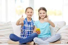 Ευτυχή κορίτσια με τη συνεδρίαση smartphone στον καναπέ Στοκ Φωτογραφία
