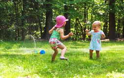 Ευτυχή κορίτσια μικρών παιδιών που παίζουν σε έναν ψεκαστήρα Στοκ Εικόνες