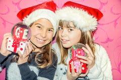 Ευτυχή κορίτσια παιδιών σε ένα δώρο σφαιρών γυαλιού εκμετάλλευσης καπέλων Χριστουγέννων Στοκ εικόνα με δικαίωμα ελεύθερης χρήσης