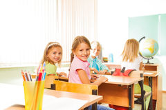 Ευτυχή κορίτσια που εξετάζουν και που κάθονται στις σειρές τα γραφεία Στοκ εικόνες με δικαίωμα ελεύθερης χρήσης