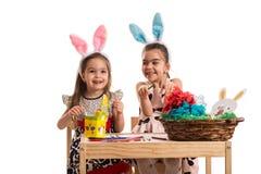 Ευτυχή κορίτσια που διακοσμούν τα αυγά Πάσχας Στοκ Φωτογραφία