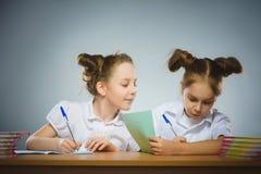 Ευτυχή κορίτσια που κάθονται στο γραφείο στο γκρίζο υπόβαθρο μαύρο σχολείο έννοιας βιβλίων ανασκόπησης copyspace Στοκ εικόνα με δικαίωμα ελεύθερης χρήσης
