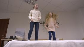Ευτυχή κορίτσια που πηδούν στο κρεβάτι απόθεμα βίντεο