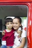 Ευτυχή κορίτσι και αγόρι στο αυτοκίνητο πυροσβεστών Στοκ Φωτογραφίες