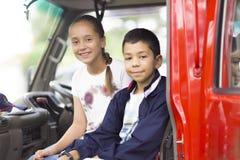 Ευτυχή κορίτσι και αγόρι στο αυτοκίνητο πυροσβεστών Στοκ Φωτογραφία
