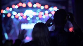 Ευτυχή κυματίζοντας χέρια γυναικών και ανδρών και χορός στο φεστιβάλ μουσικής, νυχτερινή ζωή απόθεμα βίντεο