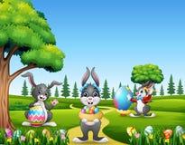Ευτυχή λαγουδάκια Πάσχας που κρατούν και που χρωματίζουν τα αυγά στοκ εικόνες
